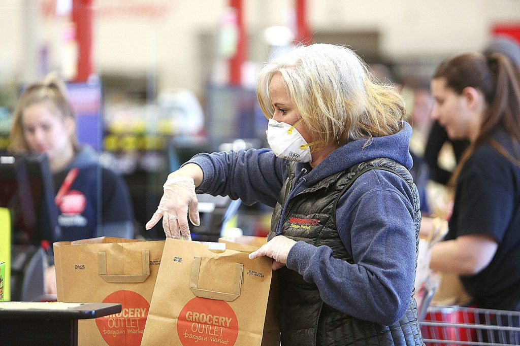 Grocery Outlet's Kasandra Berry wears an N95 mask while helping to bag groceries last week in Grass Valley.