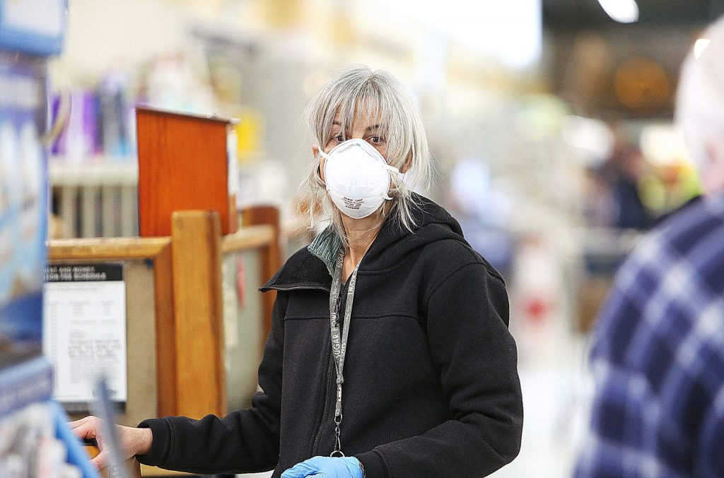 Lisa Mandelbaum wears an N95 mask as she works on mailing a pair of packages last week at SPD Market in Nevada City, before a federal recommendation to wear masks in public was announced.