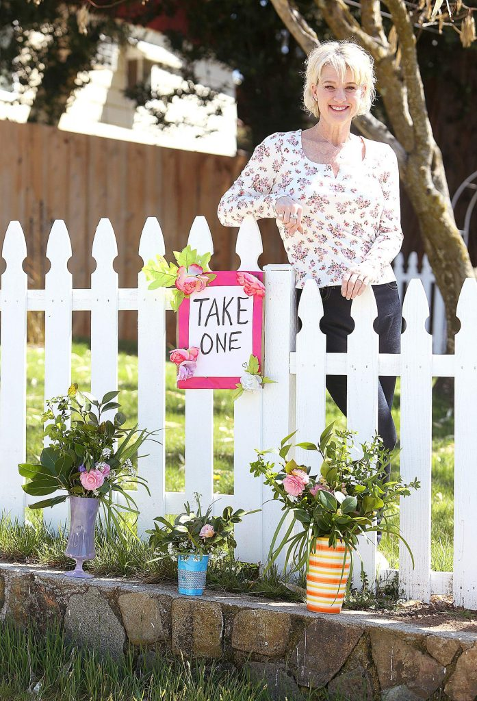 Local volunteer Angela Rule stands behind the fence of her Marshall Street home in Grass Valley where she's begun making flower bouquets for anyone to come by and take one.