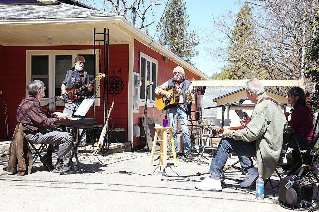 Members of a driveway jam session perform at a distance from one another off Gethsemane Street in Nevada City. Musicians Steve Miller, from left, Richard Thomas, Jeff Kane, and Lynn and Steve Rutherford.