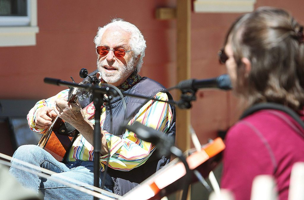 Jeff Kane of the Elderly Brothers keeps distance among members of his own band and others during a jam session on Gethsemane Street earlier this week.