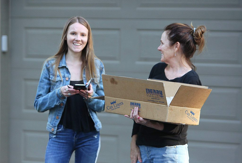 Julia Dyer and her mother Suzie Dyer smile as they prepare to head down the street to deliver burgers and shakes to their neighbors Friday evening in Nevada City.