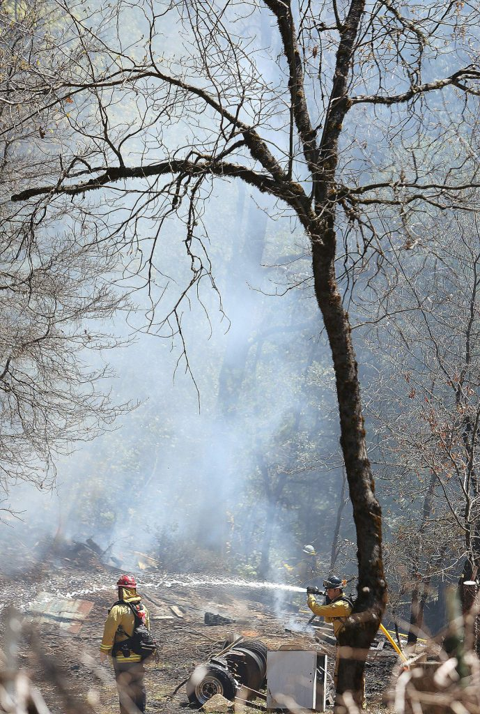Firefighters douse the escaped burn pile Thursday off Gold Starr Lane in rural Grass Valley.