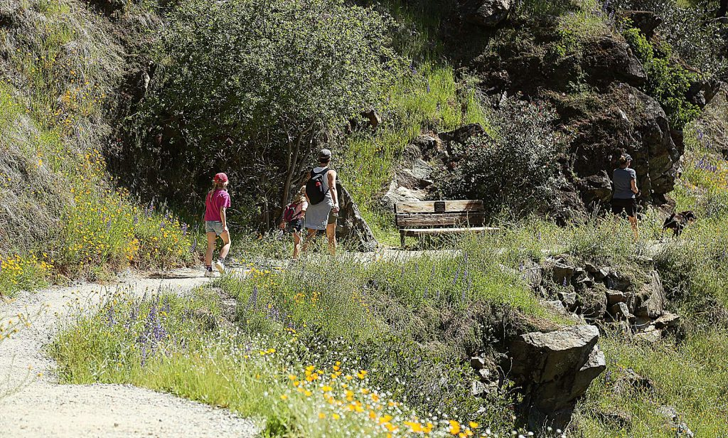 A family enjoys a leisurely walk along the Buttermilk Bend Trail Tuesday, when users along the trail were scant.