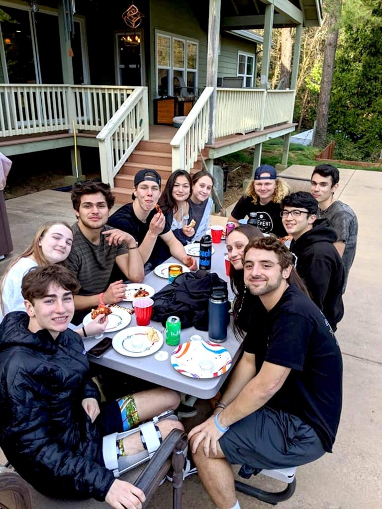 Ryan Bodine, front, with his friends at his home before the shelter-in-place order went into effect and after his stints in the hospital. After a serious snowboarding incident, Ryan is walking again without assistance.
