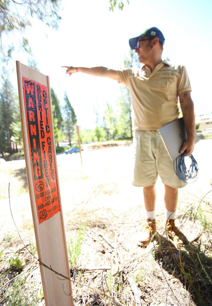 Seven Hills Business District's Robert Trent stands over an underground fiber optic cable and points towards his business, Sierra Commons Business Ignitor, where he'd like the internet line to be able to connect to.