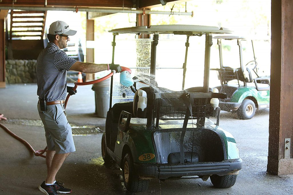 Alta Sierra County Club sales associate Jordin Tucker washes down a golf cart after it comes in, demonstrating their disinfecting procedure used on anything touched by people.