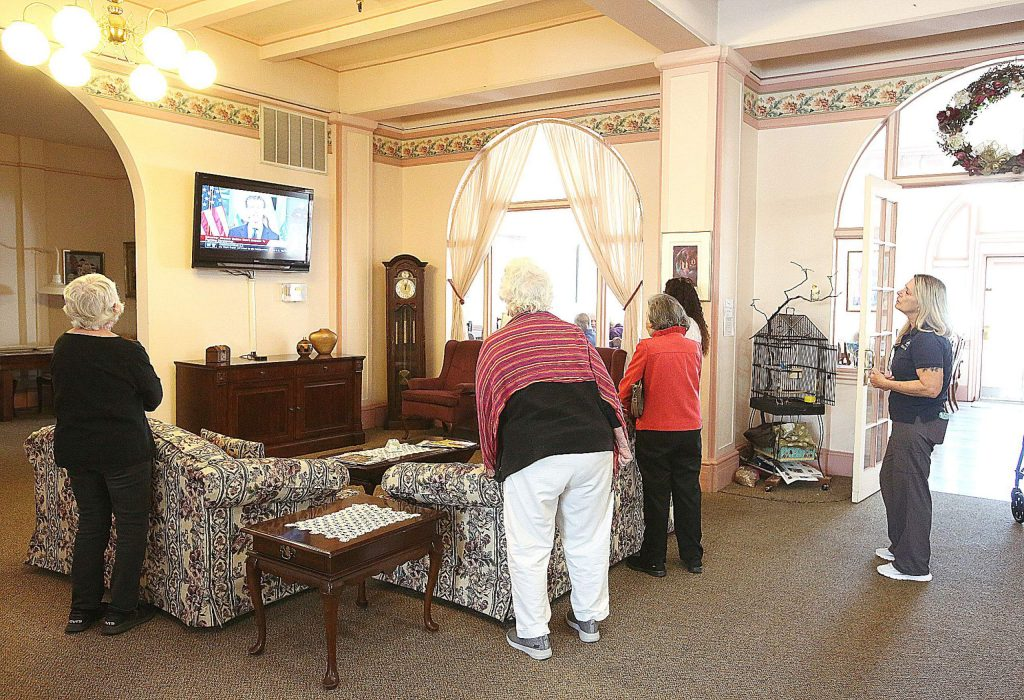 Bret Harte Retirement Inn residents and staff gather around the downstairs television during Gov. Gavin Newsom's daily noon press briefing on the coronavirus.