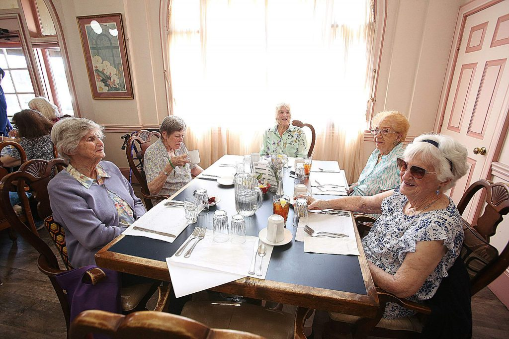 A group of friends and fellow residents gather around a table in the dining room as the wait for their skinny dipped chicken lunch.