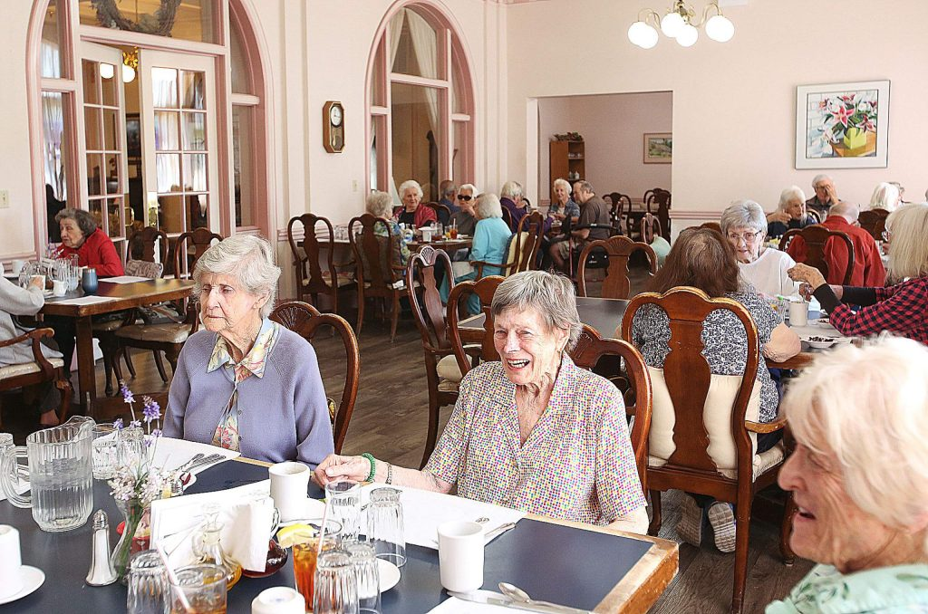 Residents of the Bret Harte Retirement Inn share a laugh around the dining room table Thursday afternoon as they await their lunch.