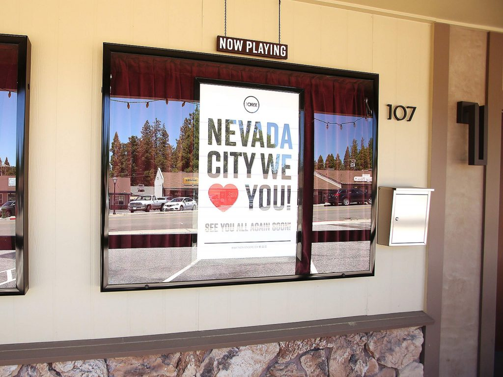 Posters send well wishes to Nevada City's residents from the front of The Onyx Theater.