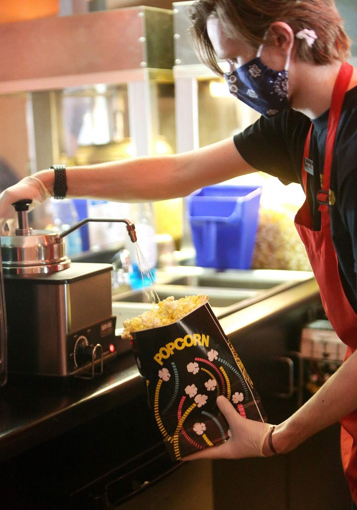 Del Oro Theater snack bar worker Logan Ingram places butter on the popcorn during the theater's first day open in 10 weeks. Though it is not currently screening films, fans of the snack bar are satisfied with the popcorn for now.
