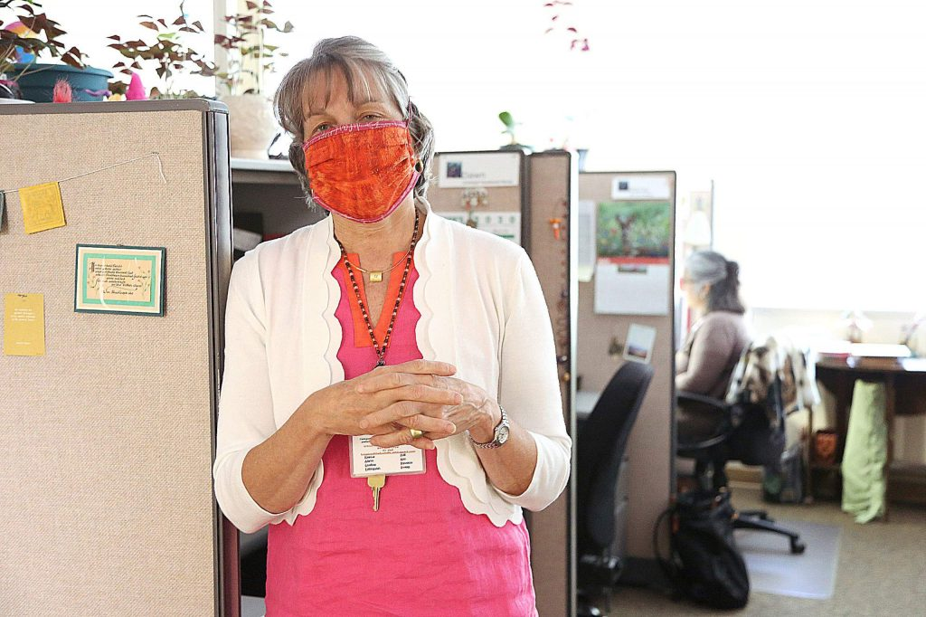 Kristen Donahue, director of marketing and development at Hospice of the Foothills, dons a nose and mouth covering while working within the Grass Valley facility.