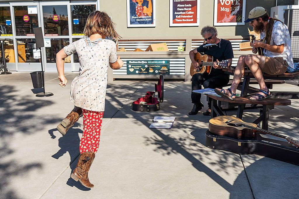 Local musician Billy Bensing (center) plays music for donations outside Briar Patch, along with Gabriel Bingham (right).