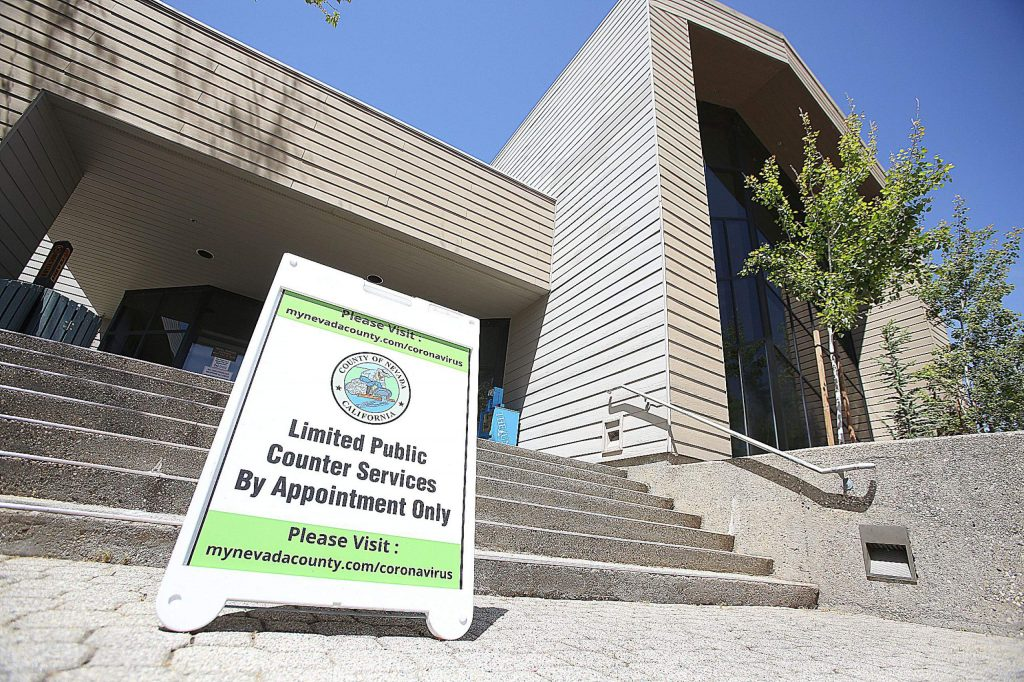 A sign letting folks know that there are limited public services greets folks at the entrance of the Rood Government Center in Nevada City.