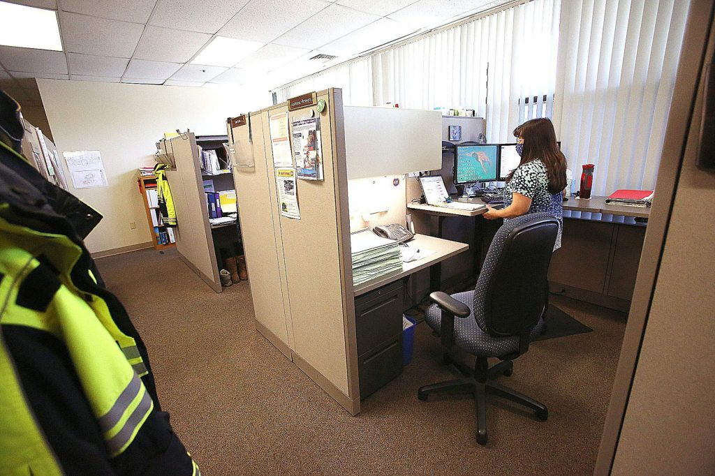 Nevada County's Antonia Powers wears her mask as she works from her cubicle at the Rood Government Center last week. Only a handful of county government employees are working in the building while many are working remotely.
