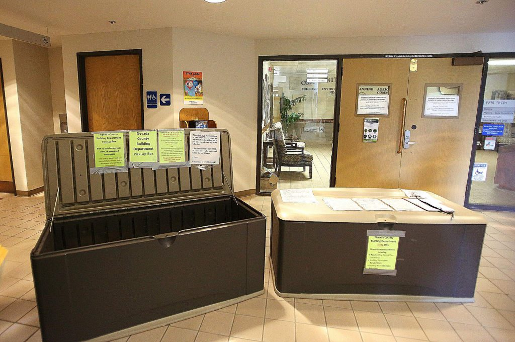 In an effort to continue to provide services through Nevada County's Building Department, drop bins for building permits and other building department business, are placed in front of the doors to the Rood Center department now closed to the public due to COVID-19.