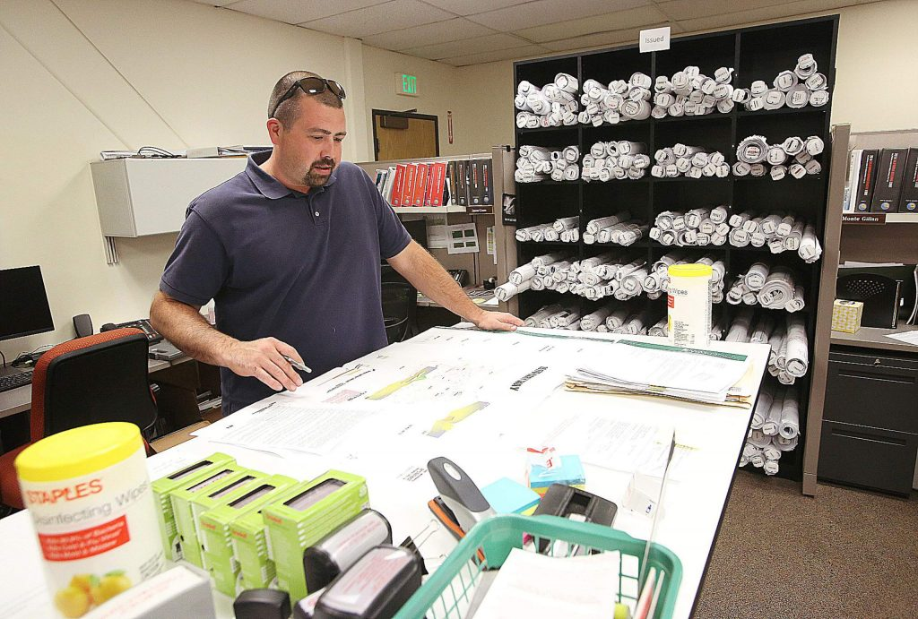 Nevada County building inspector Ben Miller looks over some plans from the county's offices at the Rood Government Center in Nevada City.