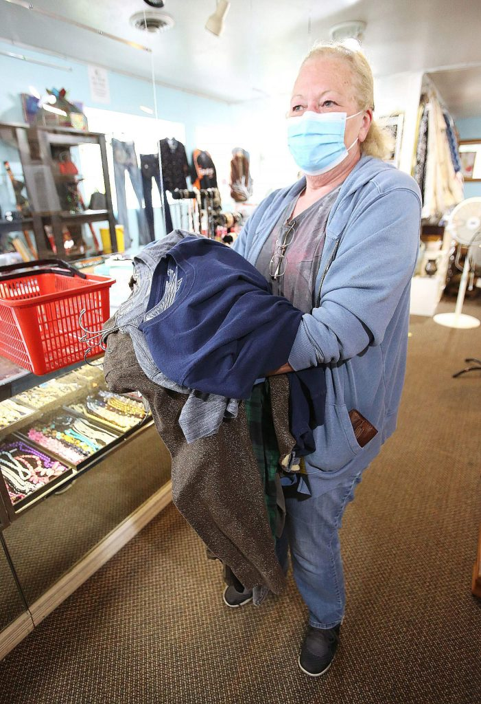Sierra Roots' Dianne Weichel dons a mask as she waits her turn in line at Hospice of the Foothills Gift and Thrift in Nevada City.