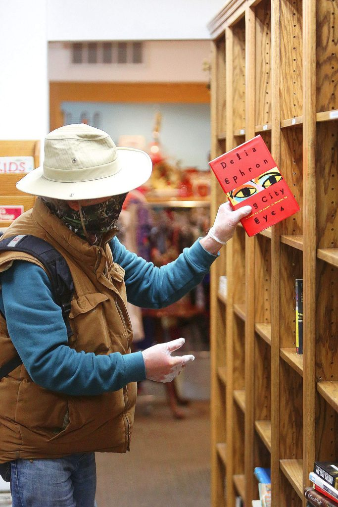 A thrift store hunter wears gloves and a face mask while perusing through the book selection at Hospice Gift and Thrift in Nevada City.