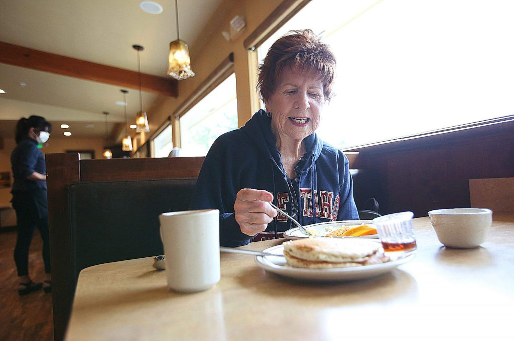 Grass Valley's Mary Johanson sits down to enjoy a breakfast meal at Humpty Dumpty's Thursday morning, its first day open after the COVID-19 shutdowns. Until plexiglass partitions can be installed, patrons will be seated at alternating booths and are asked to wear face coverings if not at their seat.