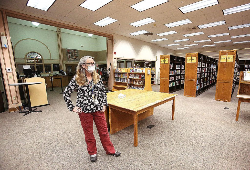 Madelyn Helling branch manager Cindy Pawlowski stands in front of the stacks of library books void of people Tuesday in Nevada City.