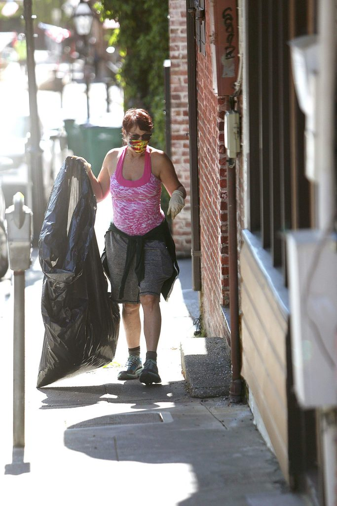 A volunteer walks up Commercial Street collecting trash in a bag during Friday morning's clean up day.