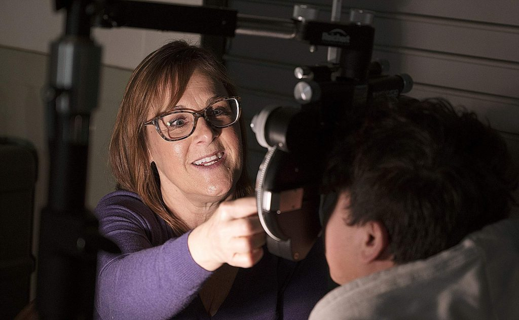 Dr. Stephanie Kirschbaum uses a eye-exam mechine to check patients' eyesight for the free health care clinic, run with help from United Way of Nevada County, at the Nevada County Fairgrounds in January. United Way of Nevada County's executive director is optimistic many local nonprofits will survive the economic downturn.