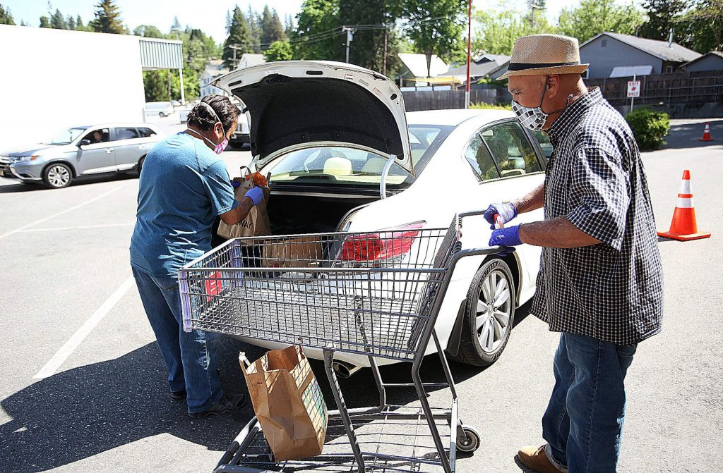 A pair of volunteers places bags of groceries into the trunk of a vehicle as others show up to receive food during the second Saturday drive-thru food distribution at Interfaith Food Ministry and sponsored in partnership with United Way.