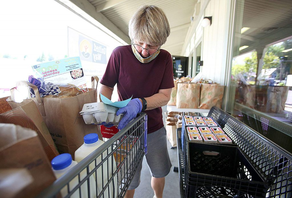 Interfaith Food Ministry volunteer Bear Stillwell places a carton of eggs into a basket during the second Saturday United Way and IFM food giveaway at 440 Henderson St. in Grass Valley. Operators have documented a two fold increase in new clients and a 25% increase in overall food distribution.