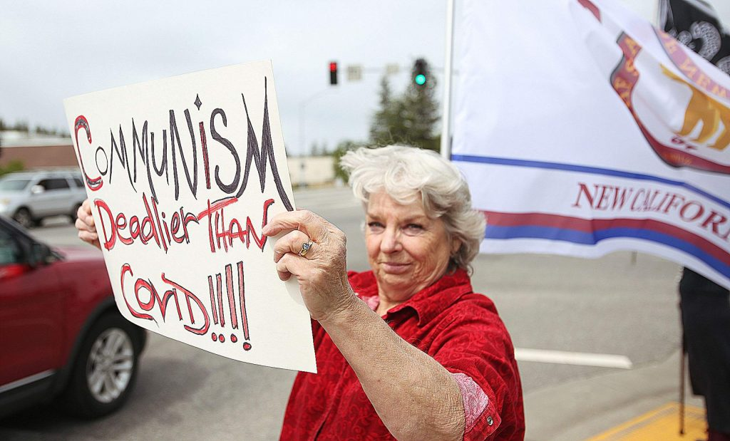 New California Nevada County chairman of the board Pam Custer holds a sign at the corner of Sutton Way and Brunswick Road Wednesday afternoon. Custer and a pair of other New California state advocates were protesting the state's closures due to COVID-19 and want the state to reopen.