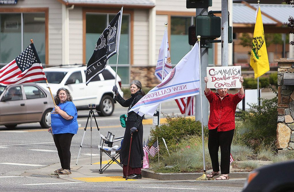 Members of New California protest for the immediate reopening of California Wednesday at the intersection of Brunswick Road and Sutton Way in Grass Valley.