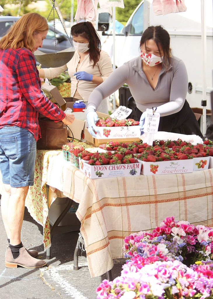 Xiong Family Farms workers, from Sutter County, help customers with their orders of strawberries and other seasonal local produce during Saturday's Grass Valley Farmers' Market.