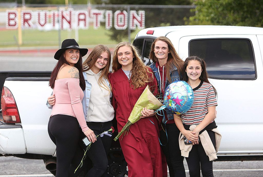 Bear River High School graduate Maddy Tyra, center, and the Tyra sisters briefly celebrate in the parking lot of the high school following Tuesday's drive-up commencement ceremony on the school's football field. Only the graduating students' families were allowed to attend the ceremony.
