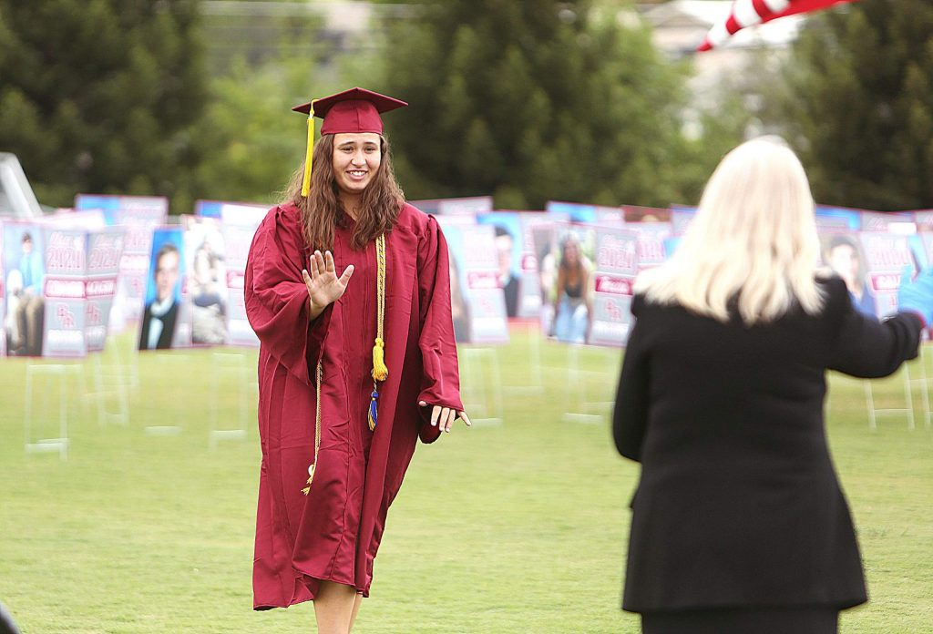Bear River High School graduate Arieal Swindell smiles and waves at a school administrator during Tuesday's graduation ceremony on the school's football field. Students and parents were given appointment times to be able to drive up and receive their diploma.