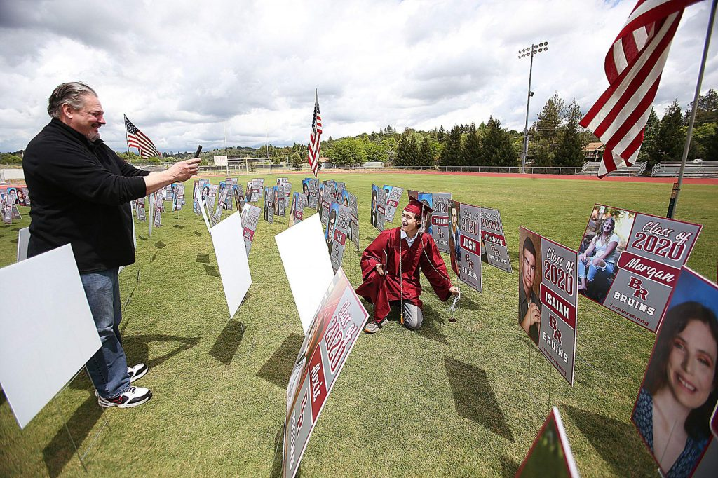 A Bear River High School graduate poses with the poster board picture of himself placed in the audience of Bear River's graduation ceremony.