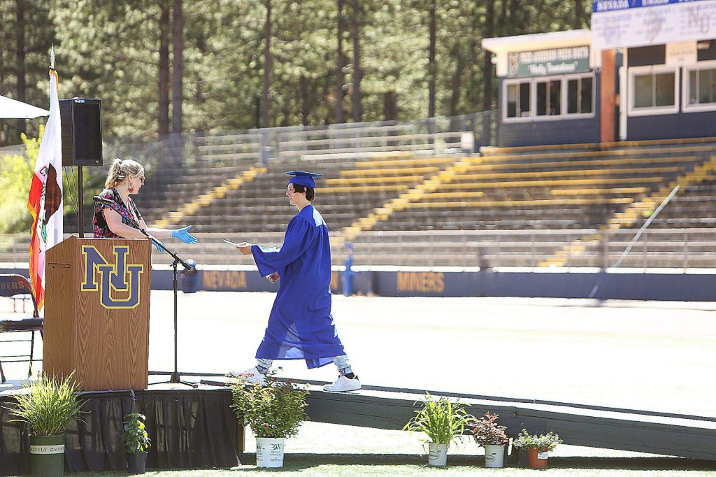 A Nevada Union High School graduate hands his name off to be read aloud to an empty Hooper Stadium during Wednesday's drive-thru ceremony.