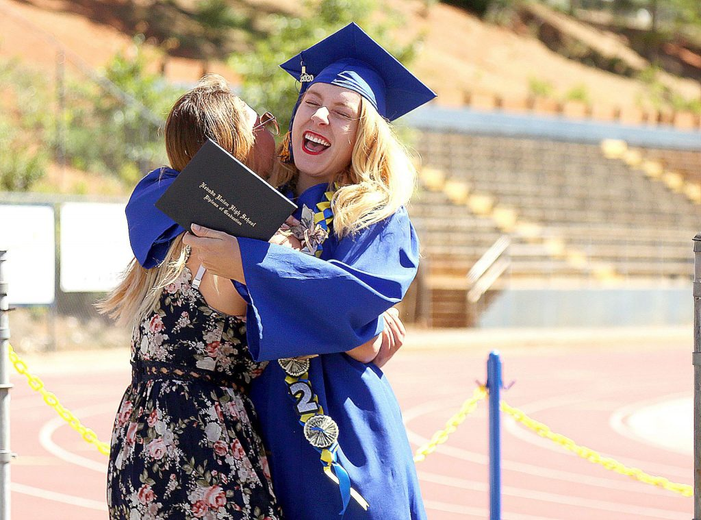 Graduate Amber Fackrell is greeted with a big hug after receiving her diploma during Wednesday's drive-thru graduation.