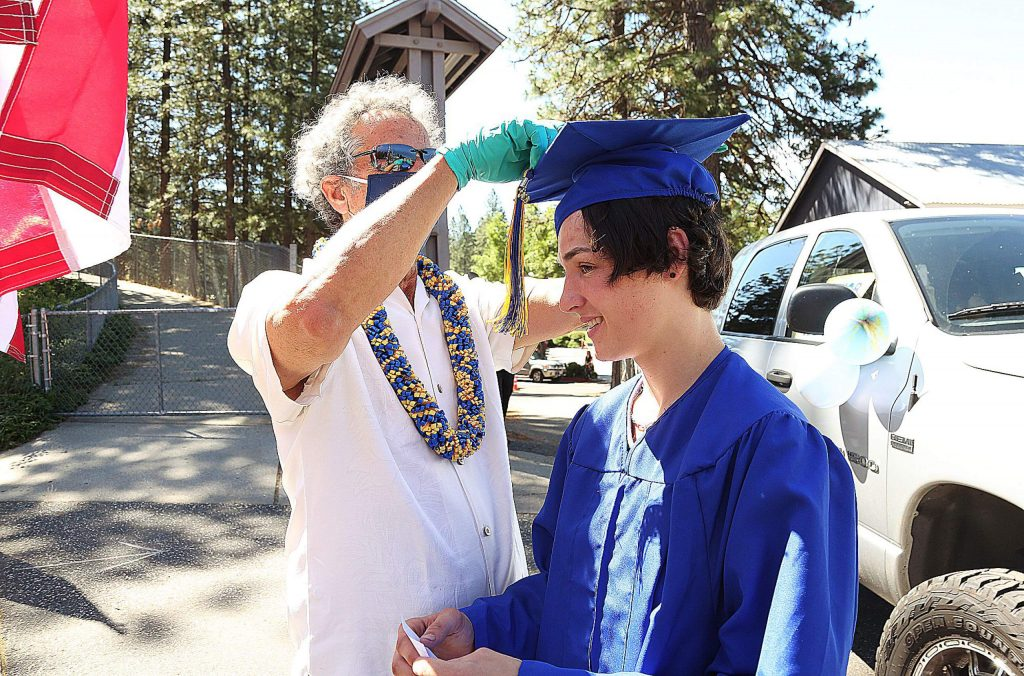 Marty Lombardi adjusts the tassel of a graduate during the 2020 drive-thru graduation ceremony at Nevada Union High School.