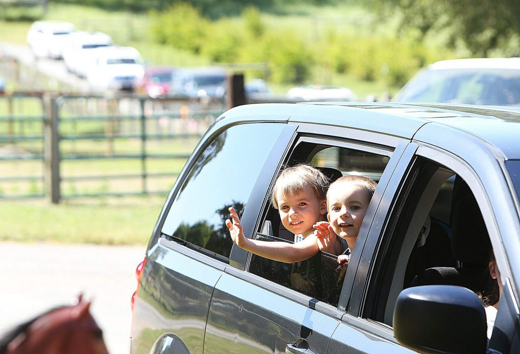A couple of Tall Pines Nursey School students wave to their teachers and friends from their vehicle during Wednesday's drive-thru tour of West Coast Equine Sports Therapy in Penn Valley.