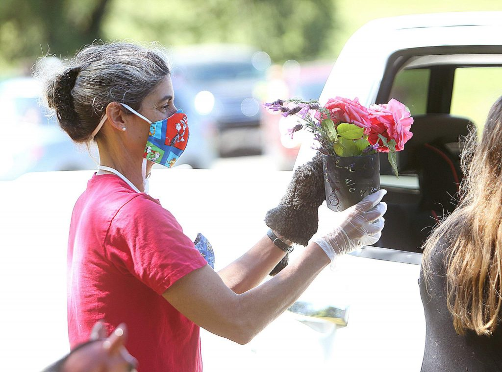 Tall Pines Nursery School's Michelle McIntosh is gifted a bouquet by one of her student's families during Wednesday morning's drive-thru style field trip at West Coast Equine Sports Therapy in Penn Valley. The field trip, originally slated to be an on-site tour, also doubled as a Mother's Day event with flowers from Grass Valley Florist and scones from Buho Bakery passed out to each vehicle.