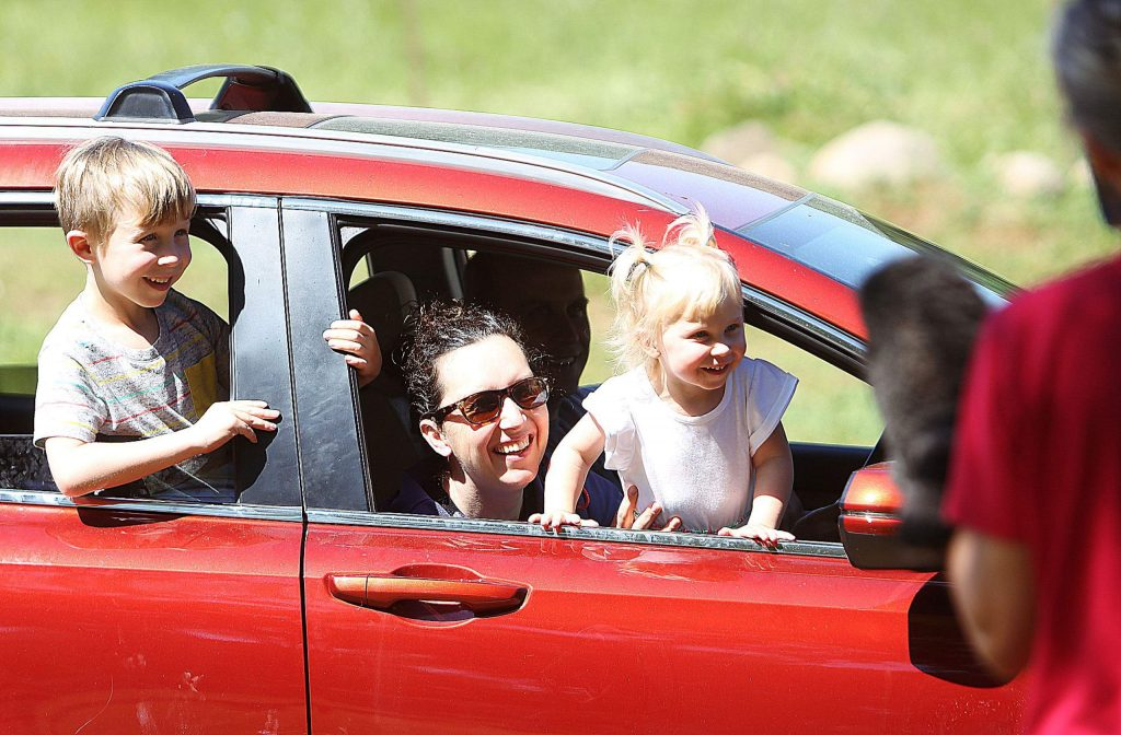 A car full of smiles approaches the Tall Pines Nursery School staff following this week's drive-thru tour of West Coast Equine Sports Therapy in Penn Valley.