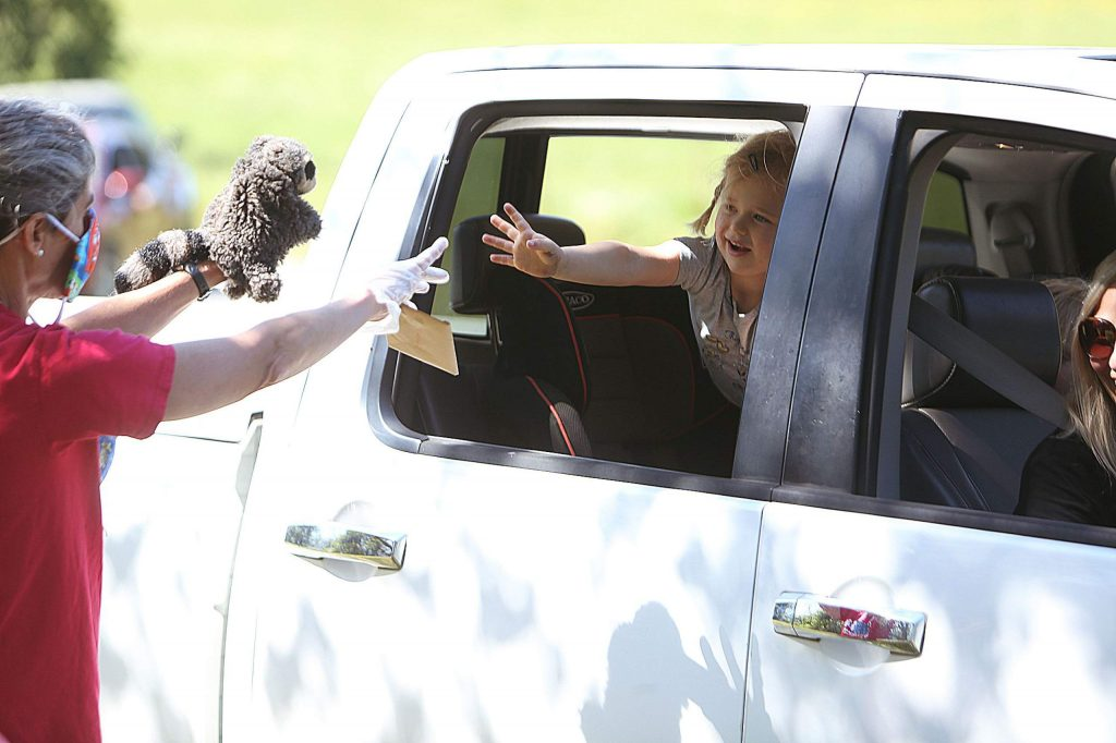A Tall Pines Nursery School student passes off a letter written to her teacher Michelle McIntosh during this week's drive-thru field trip at West Coast Equine Sports Therapy.