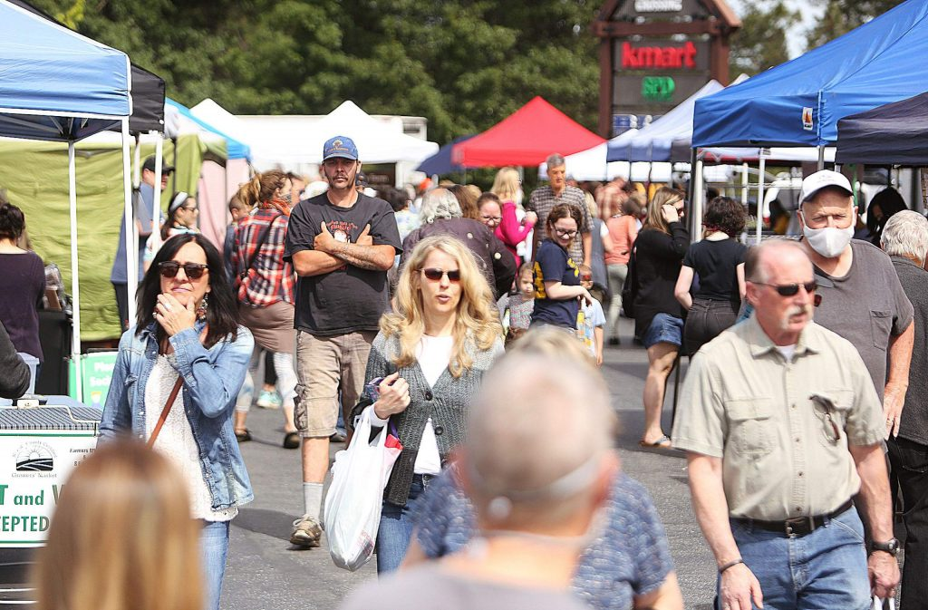 Though posted signage encourages social distancing, unbridled flows of farmer's market shoppers make it difficult to keep a 6-foot distance at the Saturday morning Grass Valley Farmer's Market at the McKnight Shopping Center parking lot. earlier this month.