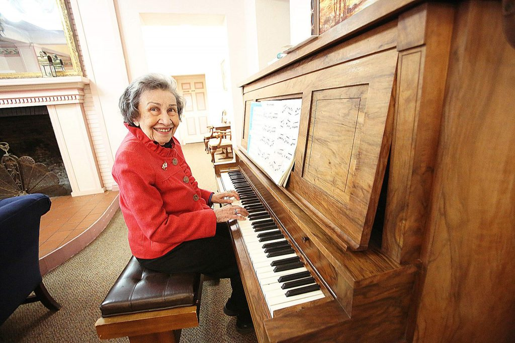 Bret Harte Retirement Inn resident Rosemary Smith smiles while playing the piano as she does every day before lunch. Smith and the other residents of the senior care facility find ways to keep amused after being on lockdown since early March.