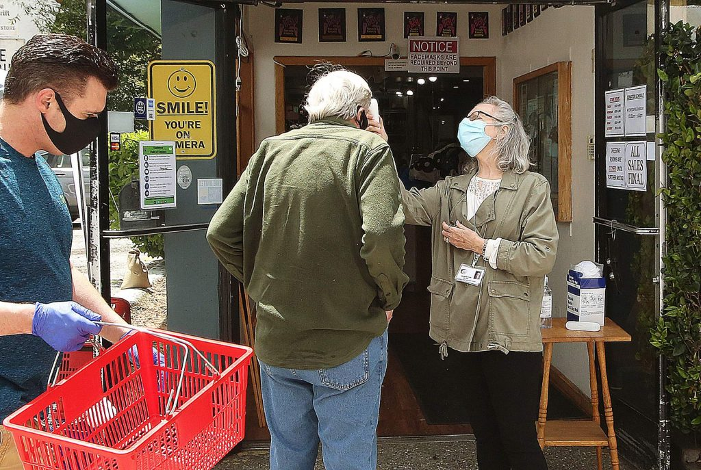 Hospice of the Foothills Gift and Thrift store employees check a customer's temperature and ask them to use a provided hand sanitizer as more businesses begin to reopen in the area.