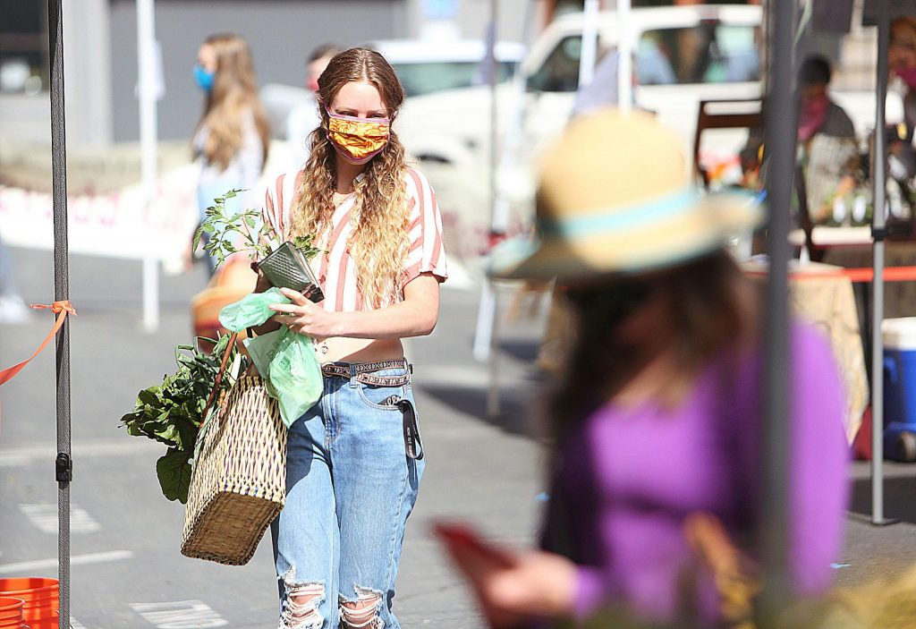 Grass Valley's Ravynn Noble wears a face mask as she carries a tomato plant and other fresh vegetables picked up during Saturday's downtown Nevada City Farmer's Market.