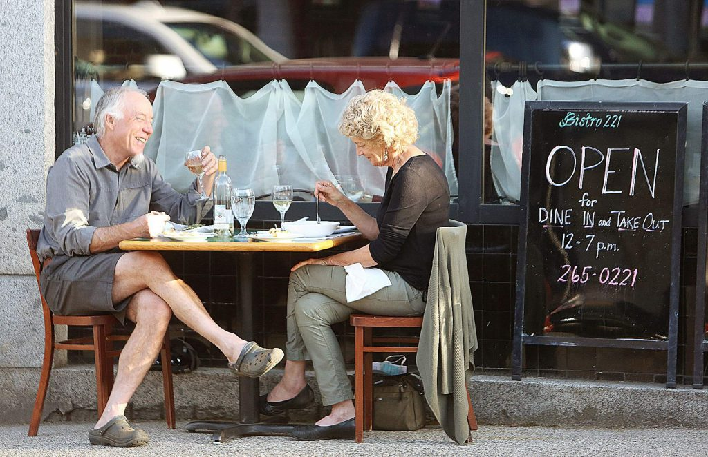Nevada City's Tony Norskog and Sara Woerner share a meal from Bistro 221 Saturday evening off of Broad Street.