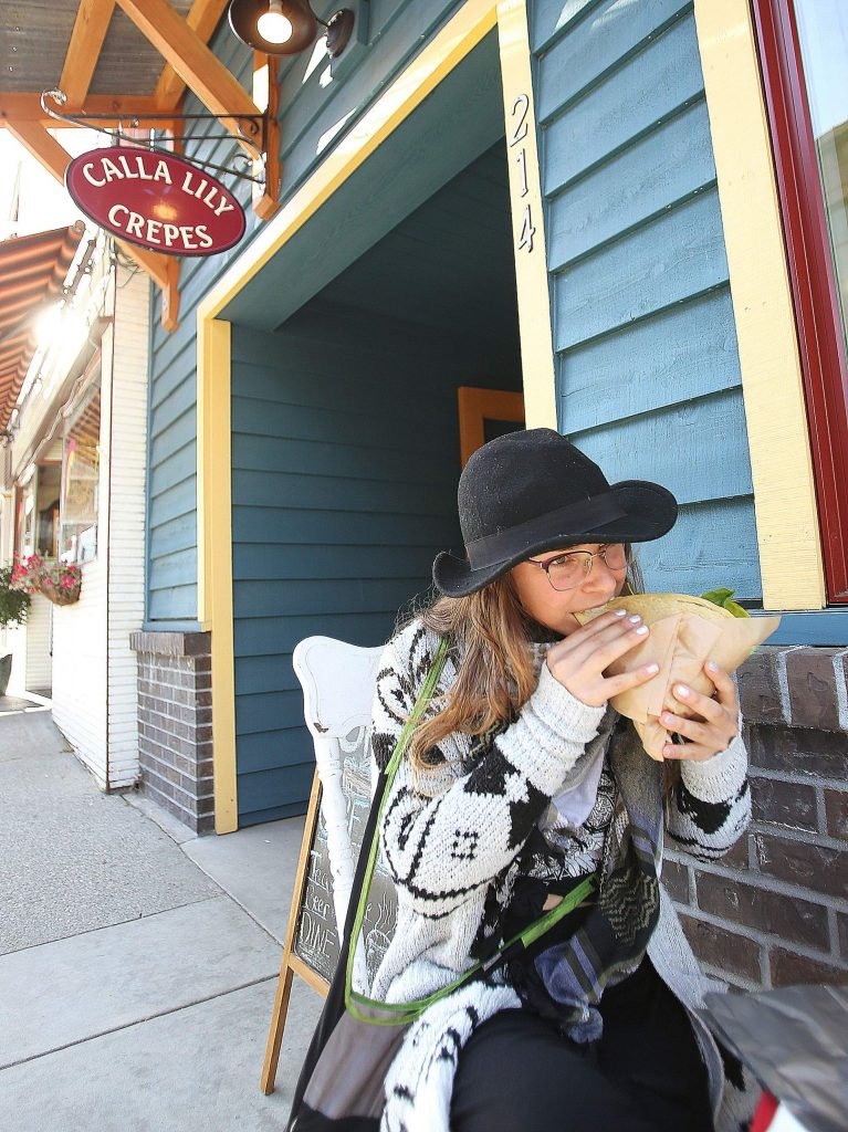 Ashley Kulik takes a bite from a crepe from Calla Lily at one of the establishment's outside eating locations. Business has been ticking up for downtown Nevada City merchants as the coronavirus restrictions ease.