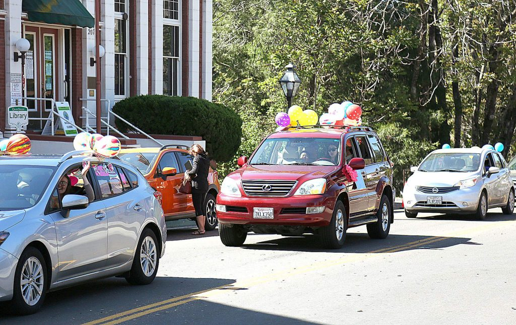 Vehicles adorned in balloons and well wishes written on their windows make their way along Mill Street in downtown Grass Valley after driving through neighborhoods where Grass Valley School District students live Friday morning.